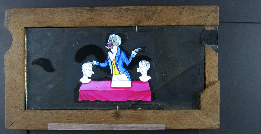 'Phrenologist', hand painted and copperplate printed slipping slide, c1890s